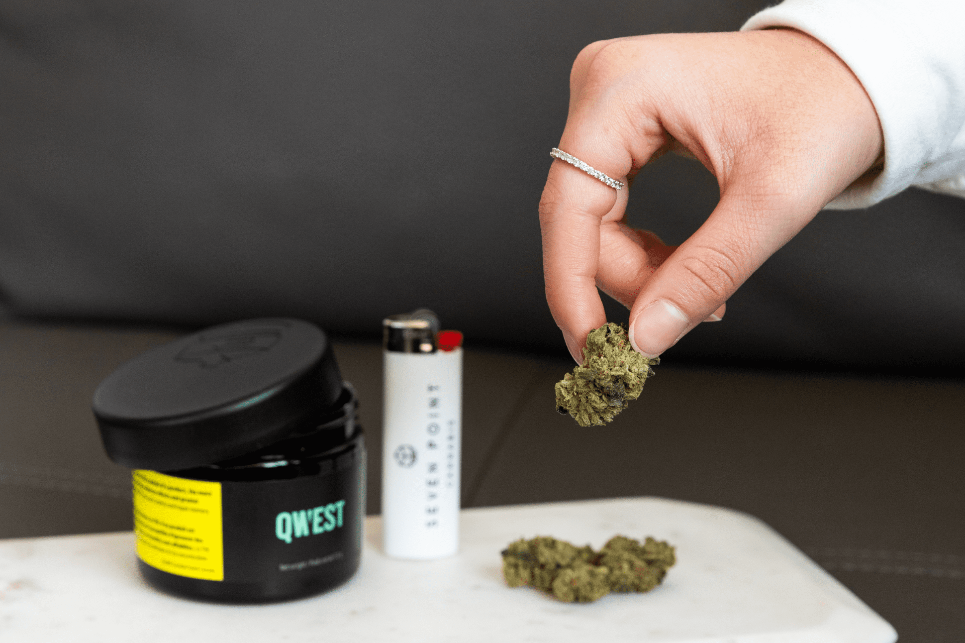 a hand picking up a nug of cannabis and a Seven Point lighter